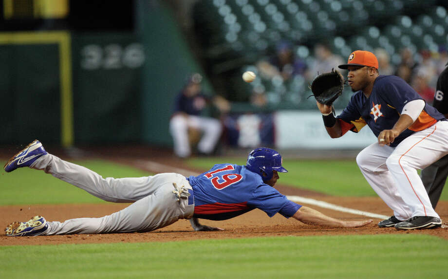 The Chicago Cubs right fielder Nate Schierholtz left, dives safely back to first base as the Houston Astros first baseman Jonathan Singleton catches the ball during the second inning of MLB exhibition game action at Minute Maid Park Saturday, March 30, 2013, in Houston . Photo: James Nielsen, Houston Chronicle / © 2013 Houston Chronicle