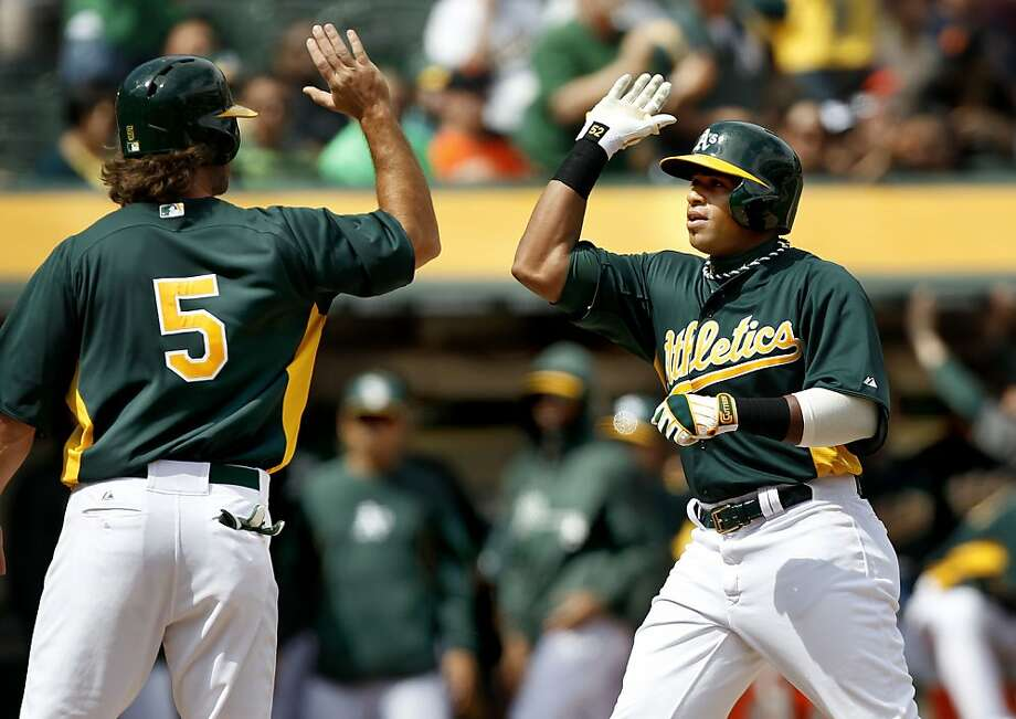 The A's Yoenis Cespedes, (52) high fives teammate John Jaso, (5) at home plate after his three run home run in the third inning, as the Oakland Athletics went on to beat the San Francisco Giants 4-3 at the O.co Coliseum in Oakland, Ca. on Saturday Mar. 30, 2013. Photo: Michael Macor, The Chronicle