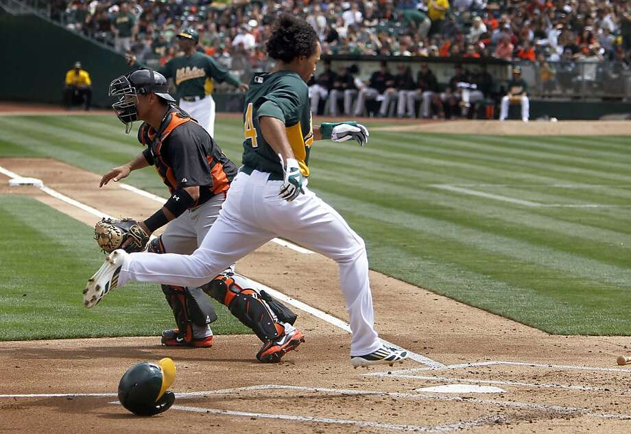 The A's Coco Crisp, (40) scores a run in the first inning off a Josh Reddick,(16) single in the first innning while Giants' catcher Guillermo Quiroz, (12) awaits the late throw as the Oakland Athletics went on to beat the San Francisco Giants 4-3 at the O.co Coliseum in Oakland, Ca. on Saturday Mar. 30, 2013. Photo: Michael Macor, The Chronicle