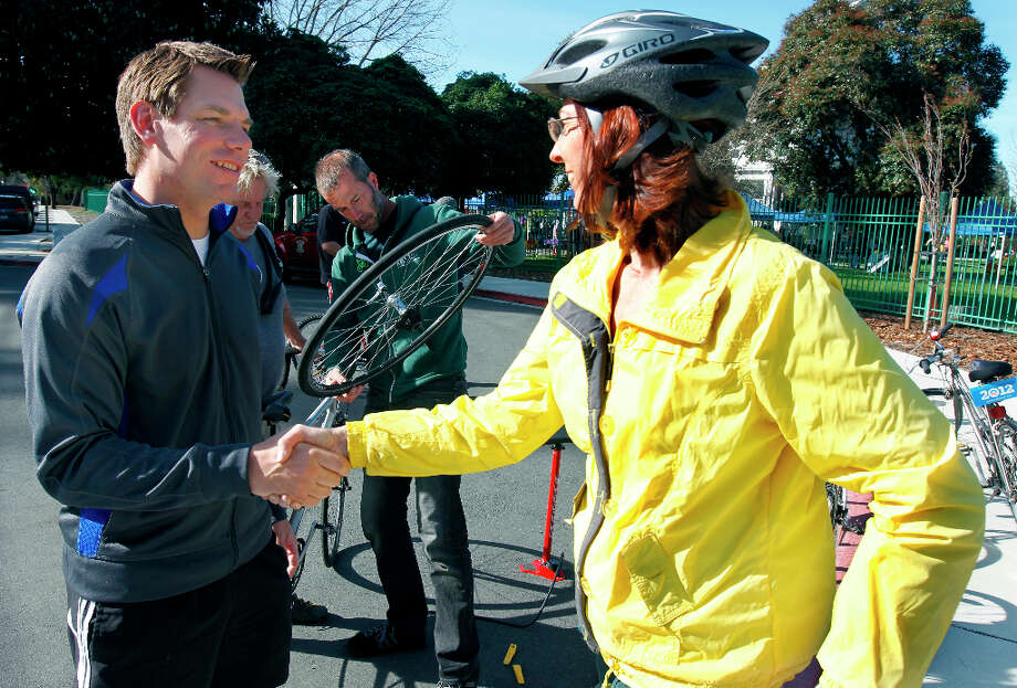 Swalwell greets Catherine Kavasch before leading constituents on a bike ride. Photo: Paul Chinn, The Chronicle / ONLINE_YES