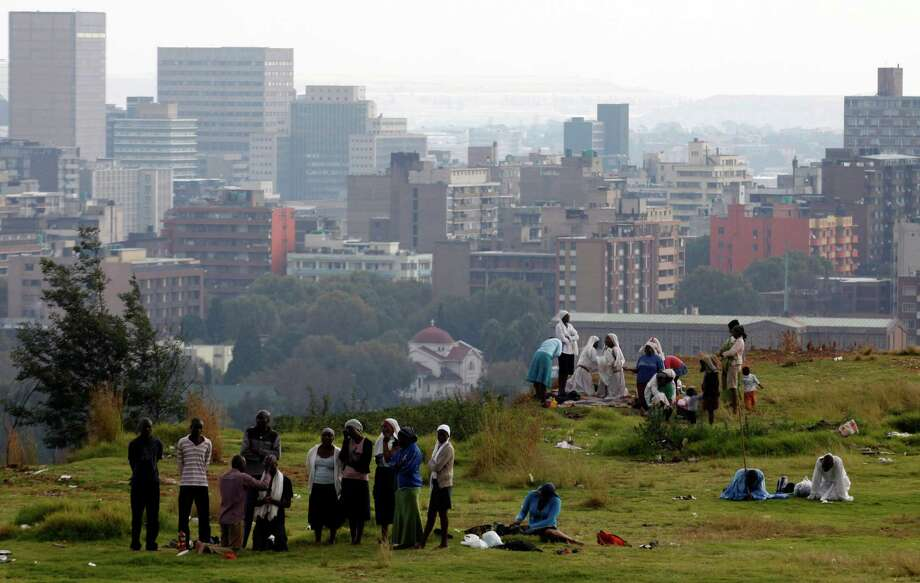 "Worshippers offer prayers for Easter and former South African president Nelson Mandela atop a hill overlooking Johannesburg, Saturday, March 30, 2013. A statement released Saturday says Mandela is breathing ""without difficulty"" after having a procedure to clear fluid in his lung area that was caused by pneumonia.  The president's office thanked all who have prayed for Mandela and his family and have sent messages of support. (AP Photo/Denis Farrell) Photo: Denis Farrell, Associated Press / AP"