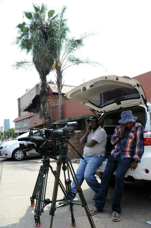 "Journalists wait outside the Mediclinic Heart Hospital on March 30, 2013 in Pretoria where former South African President Nelson Mandela is possibly hospitalized. The 94-year-old was admitted ""due to the recurrence of his lung infection"" just before midnight on March 27.  He had a build-up of fluid which had developed from the lung infection, known as a pleural effusion or ""water on the lungs"", drained from his chest. AFP PHOTO / STEPHANE DE SAKUTIN Photo: STEPHANE DE SAKUTIN, AFP/Getty Images / AFP"