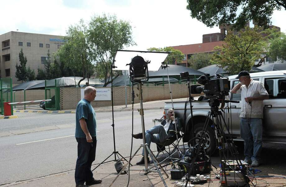 "Journalists wait outside the Mediclinic Heart Hospital on March 30, 2013 in Pretoria where former South African President Nelson Mandela is possibly hospitalized. The 94-year-old was admitted ""due to the recurrence of his lung infection"" just before midnight on March 27. Mandela was comfortable and breathing without difficulty after being treated for pneumonia, the presidency said today as the anti-apartheid icon spent a third day in hospital. AFP PHOTO / STEPHANE DE SAKUTIN Photo: STEPHANE DE SAKUTIN, AFP/Getty Images / AFP"
