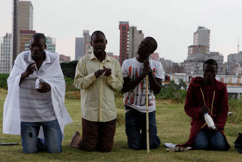 """Worshippers atop a hill overlooking Johannesburg offer Good Friday prayers and prayers for the quick recovery of former president Nelson Mandela Friday, March 29, 2013.   A lung infection that has plagued Nelson Mandela has struck again, prompting doctors to admit the 94-year-old former president to a hospital late at night. The presidency said Friday that Mandela was making """"steady progress"""" during hospital care. (AP Photo/Denis Farrell) Photo: Denis Farrell, Associated Press / AP"""