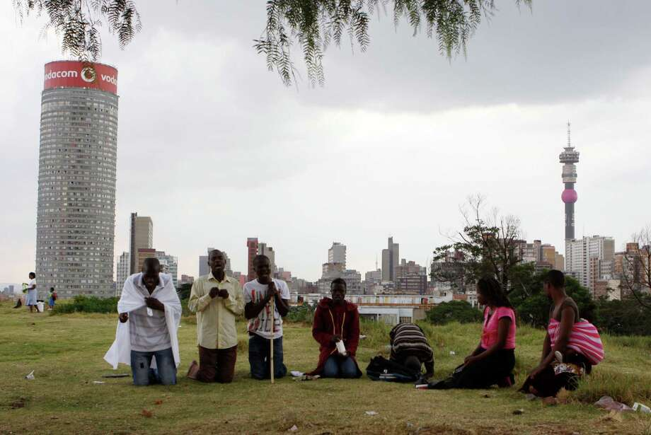 "Worshippers atop a hill overlooking Johannesburg offer Good Friday prayers and prayers for the quick recovery of former president Nelson Mandela Friday, March 29, 2013.   A lung infection that has plagued Nelson Mandela has struck again, prompting doctors to admit the 94-year-old former president to a hospital late at night. The presidency said Friday that Mandela was making ""steady progress"" during hospital care. (AP Photo/Denis Farrell) Photo: Denis Farrell, Associated Press / AP"