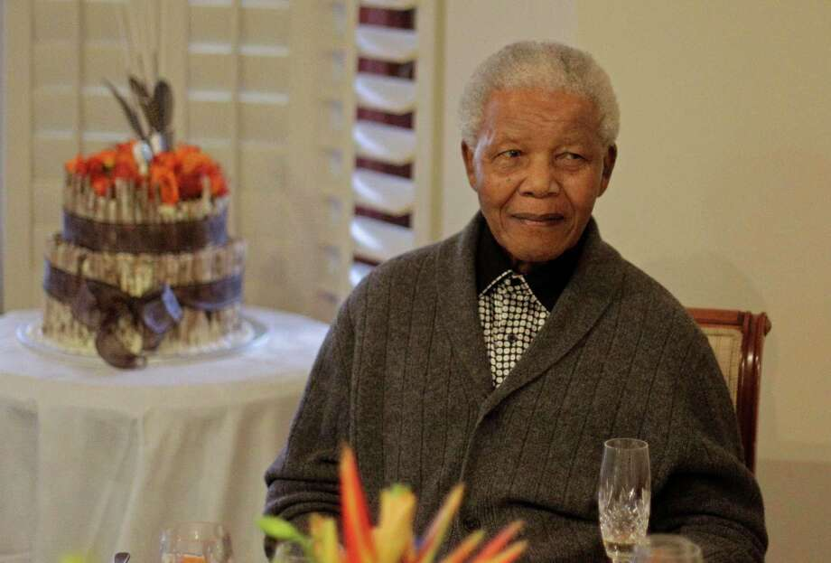 "In this Wednesday, July 18, 2012 file photo, former South African President Nelson Mandela as he celebrates his 94th birthday with family in Qunu, South Africa.  A South African official says Mandela is breathing ""without difficulty"" after having a procedure to clear fluid in his lung area that was caused by pneumonia. (AP Photo/Schalk van Zuydam, File) Photo: Schalk Van Zuydam, Associated Press / AP"