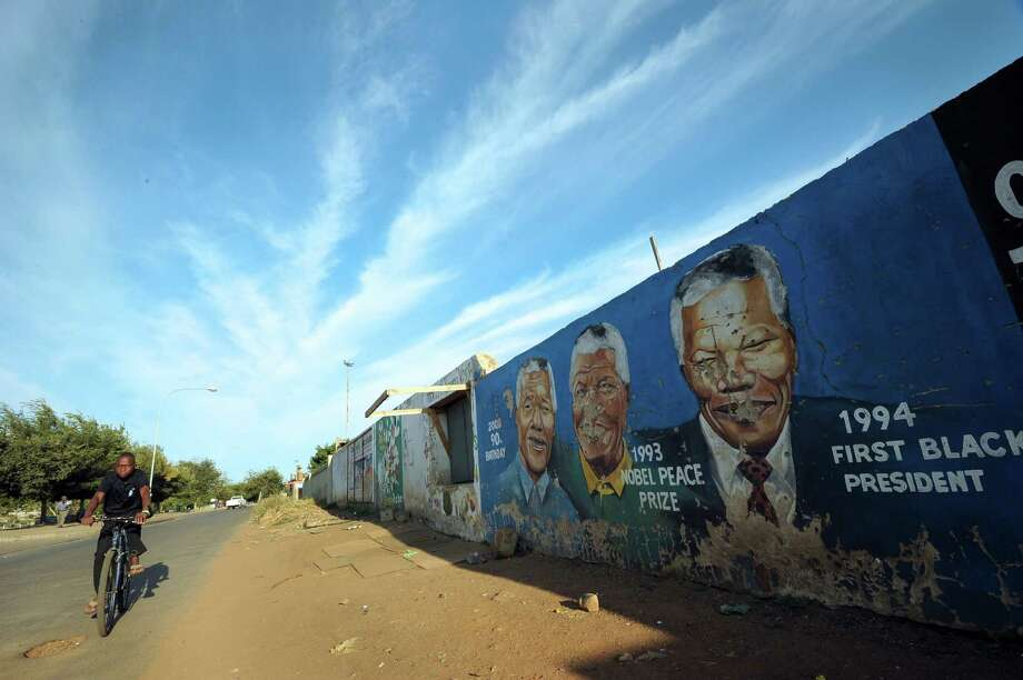 A boy rides his bike past a wall bearing painted portraits of former South African President Nelson Mandela in Soweto on March 29, 2013. Doctors said Mandela was responding positively to treatment Thursday after being readmitted to hospital with a lung infection, the latest health scare for the revered anti-apartheid icon. AFP PHOTO / ALEXANDER JOE Photo: ALEXANDER JOE, AFP/Getty Images / AFP