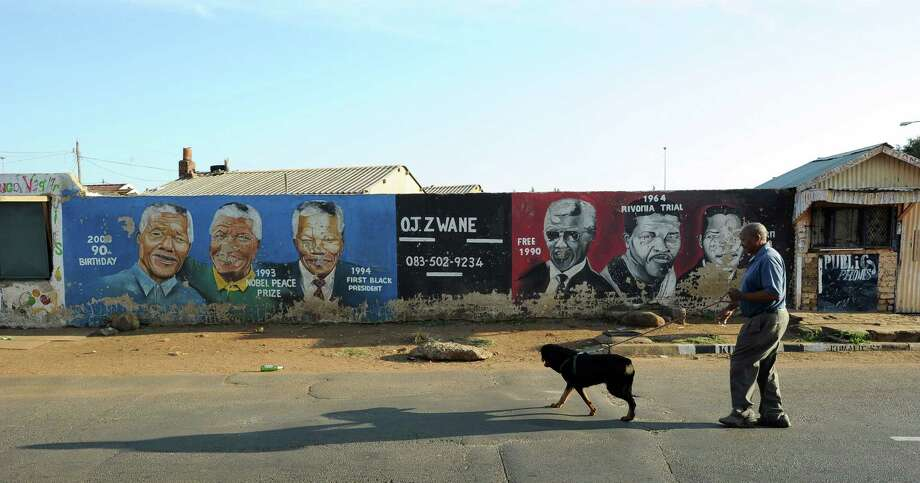 A resident of Soweto walks his dog past a wall bearing painted portraits of former South African President Nelson Mandela in Soweto on March 29, 2013. Doctors said Mandela was responding positively to treatment Thursday after being readmitted to hospital with a lung infection, the latest health scare for the revered anti-apartheid icon. Photo: ALEXANDER JOE, AFP/Getty Images / AFP