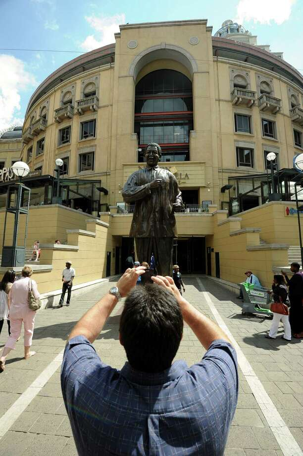 """A man takes a picture of a giant statue representing former South Africa's president Nelson Mandela at Mandela's square on March 29, 2013 in Sandton.  Mandela's latest health scare has left South Africans grappling with the frailty of  their national hero and his """"Rainbow Nation"""". The anti-apartheid icon spent his second day in hospital for a recurring lung infection. AFP PHOTO / ALEXANDER JOE Photo: ALEXANDER JOE, AFP/Getty Images / AFP"""