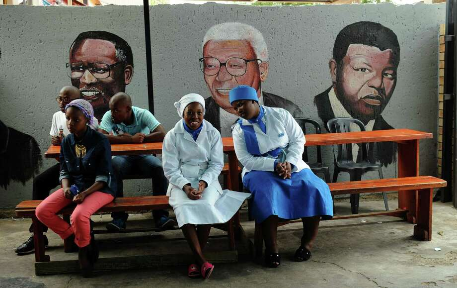"Residents of Soweto wait for their take-away food at a restaurant in Soweto on March 29, 2013 in front of a wall bearing painted portraits of former South African President Nelson Mandela (R) and anti-apartheid activists and ANC members Walter Sisulu (C) and Oliver Tambo.  Nelson Mandela was ""in good spirits"" and making steady progress today as he spent a second day in hospital for a lung infection, in the latest health scare for the revered peace icon, South Africa's presidency said. AFP PHOTO / ALEXANDER JOE Photo: ALEXANDER JOE, AFP/Getty Images / AFP"