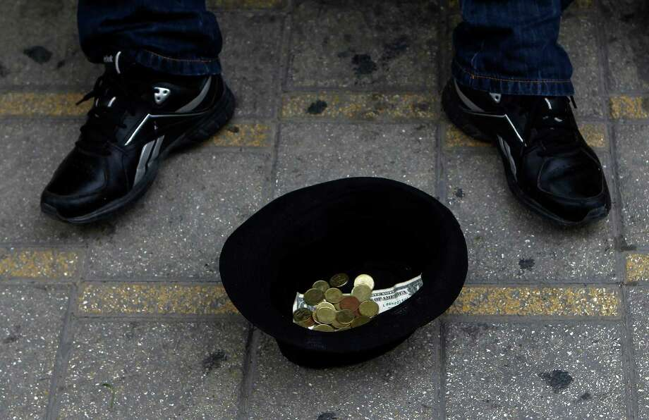 A hat with money belonging to a musician, is seen on the ground as he plays music at the main shopping street in central capital Nicosia, Cyprus, on Saturday, March 30, 2013. Big depositors at Cyprus' largest bank may be forced to accept losses of up to 60 percent, far more than initially estimated under the European rescue package to save the country from bankruptcy, officials said Saturday. (AP Photo/Petros Karadjias) Photo: Petros Karadjias