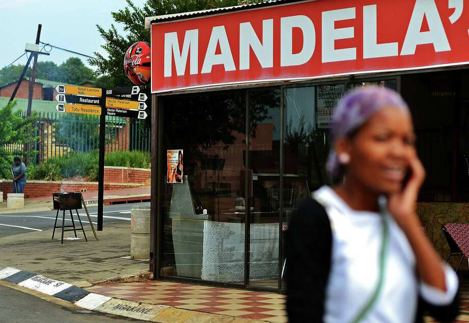 "A local Soweto resident walks past a restaurant bearing the name of former South African President Nelson Mandela in Soweto on March 30, 2013. Mandela is spending his third day in hospital after making ""steady progress"" for a recurring lung infection. Messages of concern for the ailing 94-year-old, one of the towering figures of modern history, have poured in since his admission late on March 27.  AFP PHOTO/Carl de Souza Photo: CARL DE SOUZA, AFP/Getty Images / AFP"