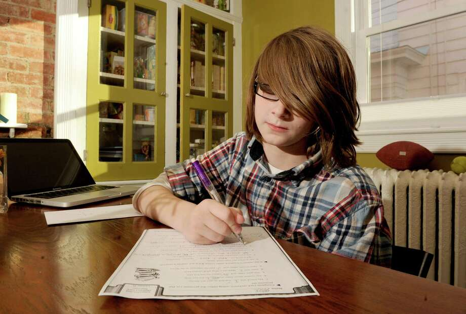 Max Powers, 10, does his homework at his home on Tuesday, March 26, 2013 in Albany, N.Y. His mom, Jennifer Goodall, is thinking about taking him out of public schools because of the increase in high-stakes testing. (Lori Van Buren / Times Union) Photo: Lori Van Buren