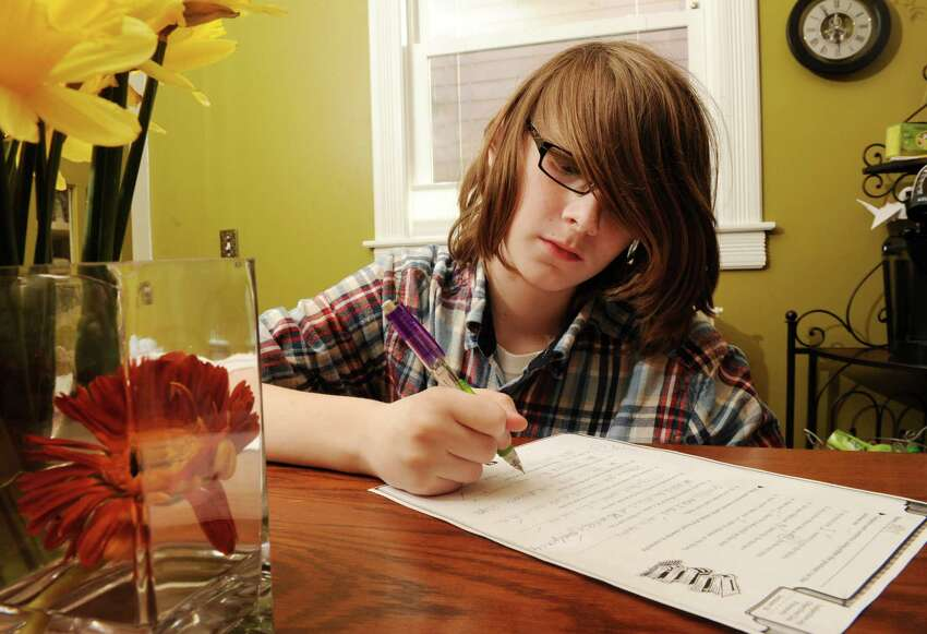 Max Powers, 10, does his homework at his home on Tuesday, March 26, 2013 in Albany, N.Y. His mom, Jennifer Goodall, is thinking about taking him out of public schools because of the increase in high-stakes testing. (Lori Van Buren / Times Union)