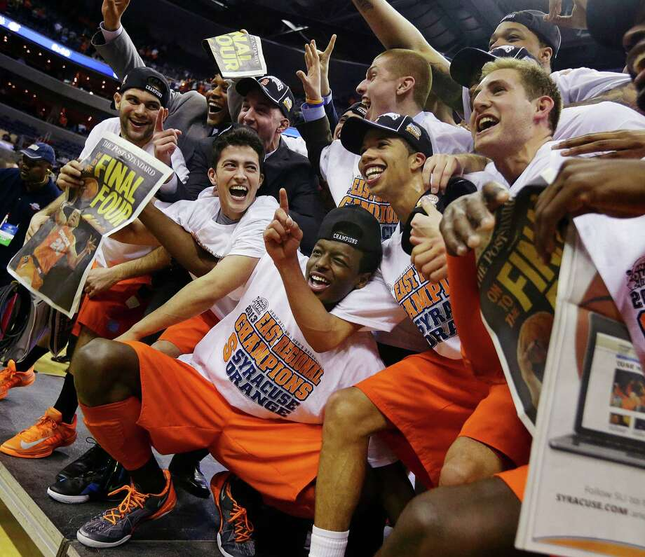 Syracuse players and coaches celebrate for photographers after their 55-39 win over Marquette in the East Regional final in the NCAA men's college basketball tournament, Saturday, March 30, 2013, in Washington. (AP Photo/Pablo Martinez Monsivais) Photo: Pablo Martinez Monsivais, Associated Press / AP