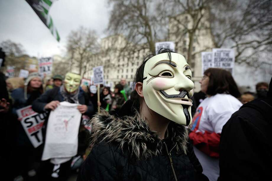 "A protestor wears a mask while demonstrating against the proposed ""bedroom tax"" gather in Trafalgar Square before marching to Downing Street on March 30, 2013 in London, England. Welfare groups are protesting the government's plans to cut benefits where families have surpassed the number of rooms they require. Photo: Matthew Lloyd, Getty Images / 2013 Getty Images"