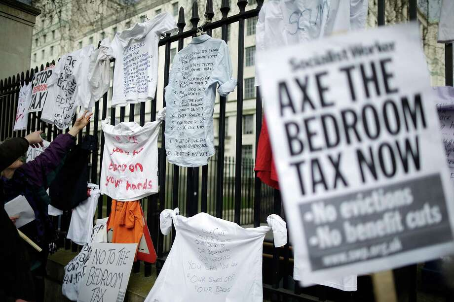 "Protestors hang signs on the gates as they demonstrate against the proposed ""bedroom tax"" gather in Trafalgar Square before marching to Downing Street on March 30, 2013 in London, England. Photo: Matthew Lloyd, Getty Images / 2013 Getty Images"