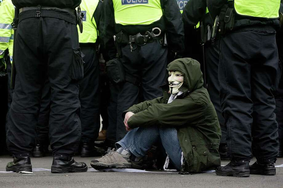 """A man sits down in protest as campaigners demonstrating against the proposed """"bedroom tax"""" gather outside Downing Street on March 30, 2013 in London, England. Photo: Matthew Lloyd, Getty Images / 2013 Getty Images"""