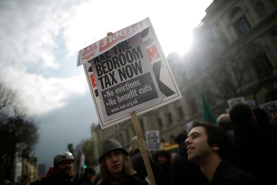 """A protestor holds a sign while demonstrating against the proposed """"bedroom tax"""" gather in Trafalgar Square before marching to Downing Street on March 30, 2013 in London, England. Photo: Matthew Lloyd, Getty Images / 2013 Getty Images"""