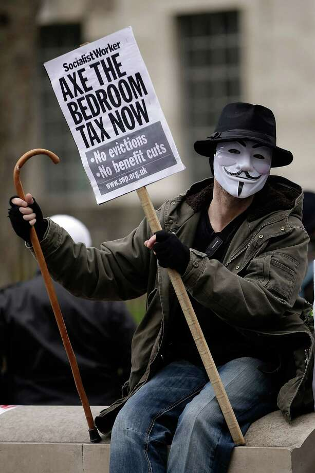 "A protestor wears a mask holding a cane and sign while demonstrating against the proposed ""bedroom tax"" gather in Trafalgar Square before marching to Downing Street on March 30, 2013 in London, England. Photo: Matthew Lloyd, Getty Images / 2013 Getty Images"