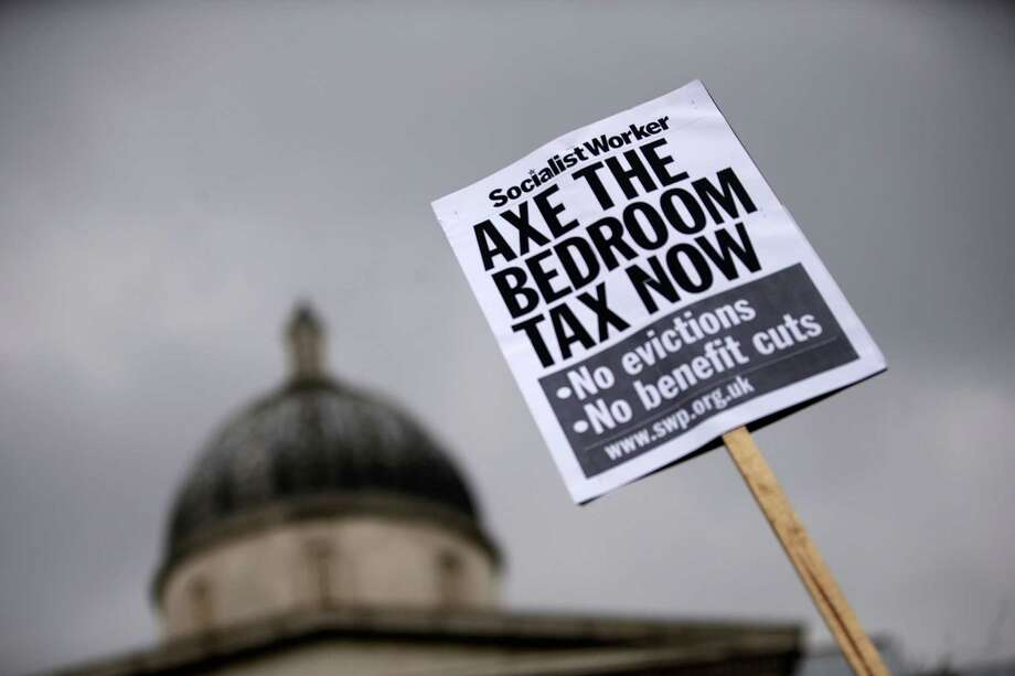 "A protestor holds a sign while demonstrating against the proposed ""bedroom tax"" gather in Trafalgar Square before marching to Downing Street on March 30, 2013 in London, England. Photo: Matthew Lloyd, Getty Images / 2013 Getty Images"