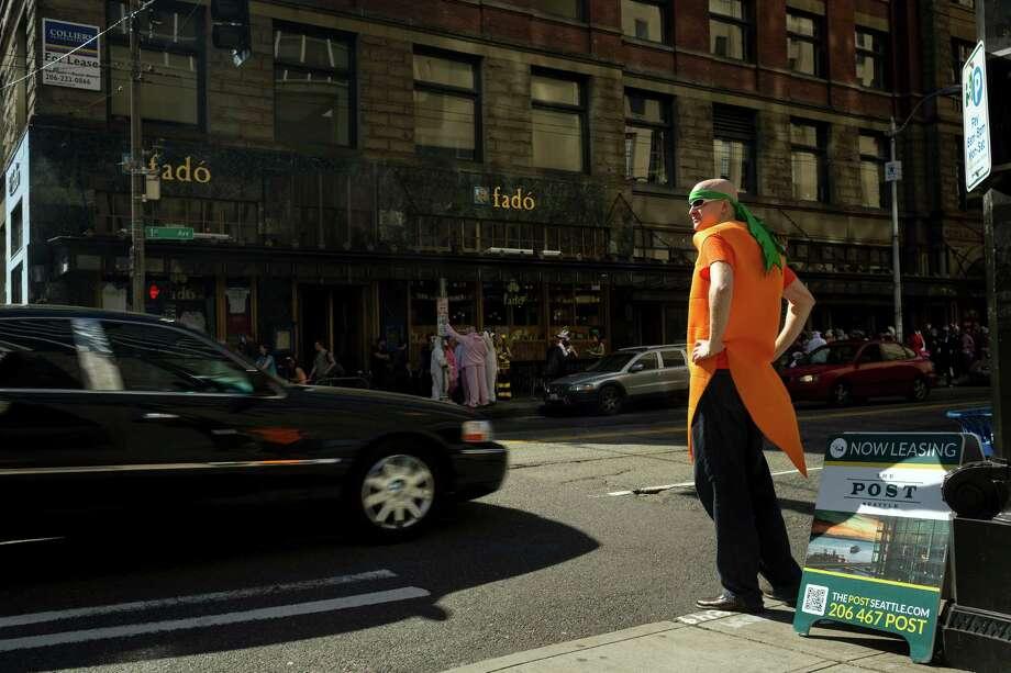 A man dressed as a carrot waits to cross the street to go to Fado. Photo: JORDAN STEAD / SEATTLEPI.COM