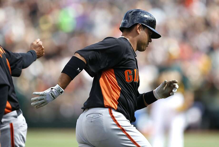 The Giants' Guillermo Quiroz, (12) rounds third base after hitting a three run home run in the seventh inning as the Oakland Athletics went on to beat the San Francisco Giants 4-3 at the O.co Coliseum in Oakland, Ca. on Saturday Mar. 30, 2013. Photo: Michael Macor, The Chronicle