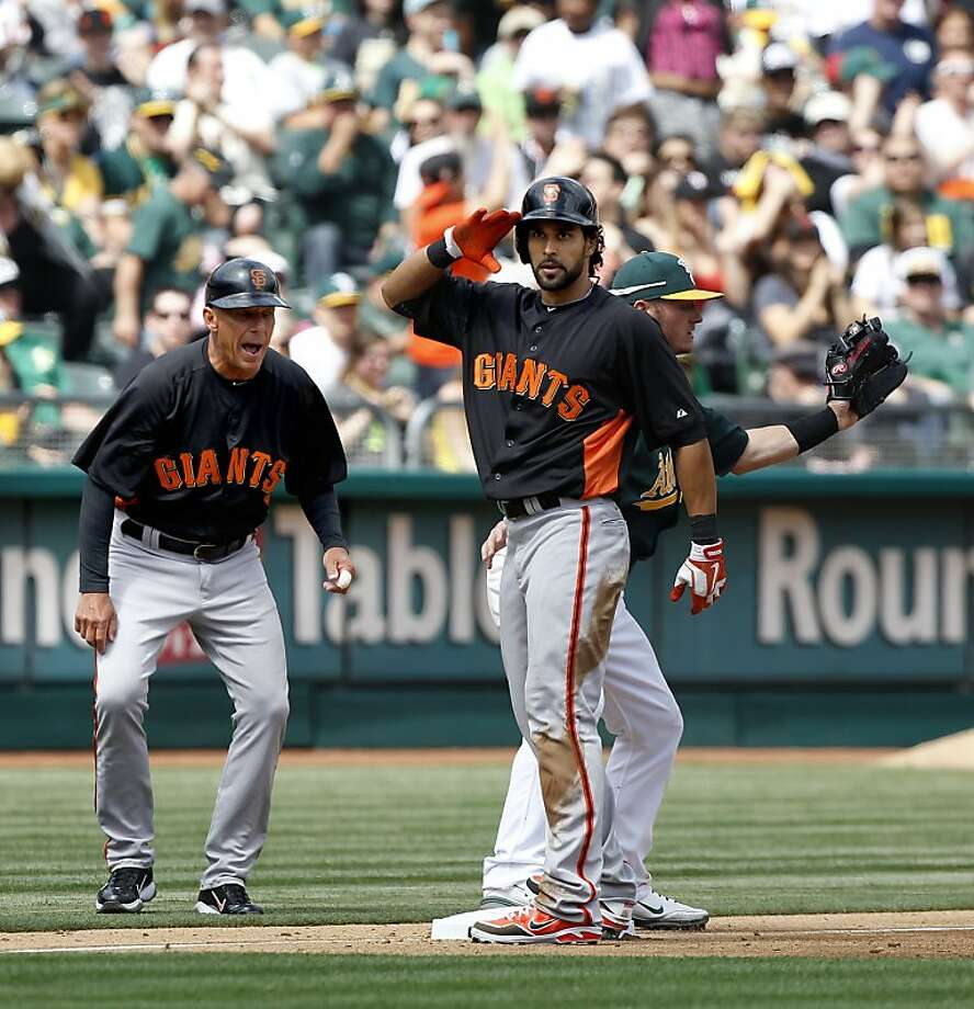 The Giants' Angel Pagan, (16) salutes his dugout after a triple in the third inning as third base coach Tim Flannery shows his excitement, as the Oakland Athletics went on to beat the San Francisco Giants 4-3 at the O.co Coliseum in Oakland, Ca. on Saturday Mar. 30, 2013. Photo: Michael Macor, The Chronicle