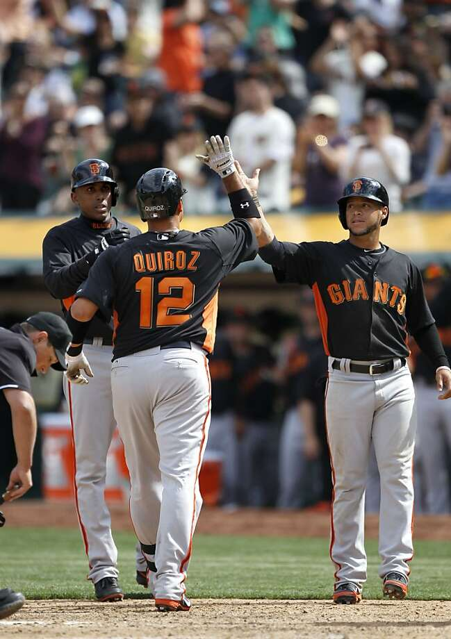 The Giants' Guillermo Quiroz, (12) hits a three run home run in the seventh inning driving in Joaquin Arias, (13-left) and Gregor Blanco, (7) as the Oakland Athletics went on to beat the San Francisco Giants 4-3 at the O.co Coliseum in Oakland, Ca. on Saturday Mar. 30, 2013. Photo: Michael Macor, The Chronicle