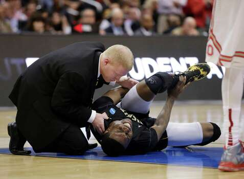 Wichita State's Cleanthony Early, right, is examined after suffering an injury during the second half of the West Regional final against Ohio State in the NCAA men's college basketball tournament, Saturday, March 30, 2013, in Los Angeles. (AP Photo/Mark J. Terrill) Photo: Mark J. Terrill, Associated Press / AP