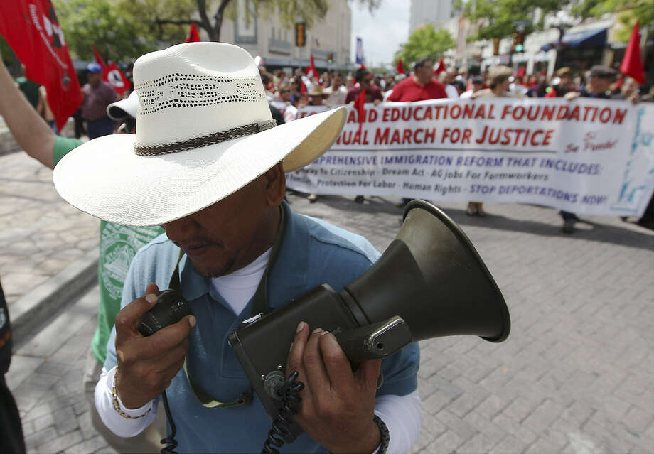 Jaime Rios calls out to marchers with the original bullhorn used by famed workers rights activist César Chávez during the 17th annual César Chávez March for Justice through downtown San Antonio. Photo: Photos By Kin Man Hui / San Antonio Express-News