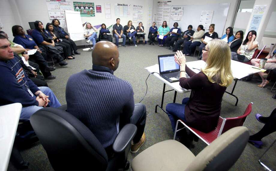 Anne Thomas (right, seated at table), a clinical psychologist in charge of the program, meets with Bexar County probation officials discuss details about the first group of girls who will occupy the new facility. Photo: William Luther / San Antonio Express-News