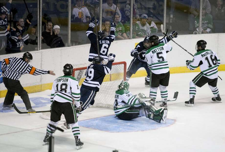 Yale teammates celebrating after scoring a goal against North Dakota in the third period of their NCAA college hockey regional championship game, Saturday, March 30, 2013, in Grand Rapids, Mich. Yale won 4-1. (AP Photo/The Grand Rapids Press, Latara Appleby)