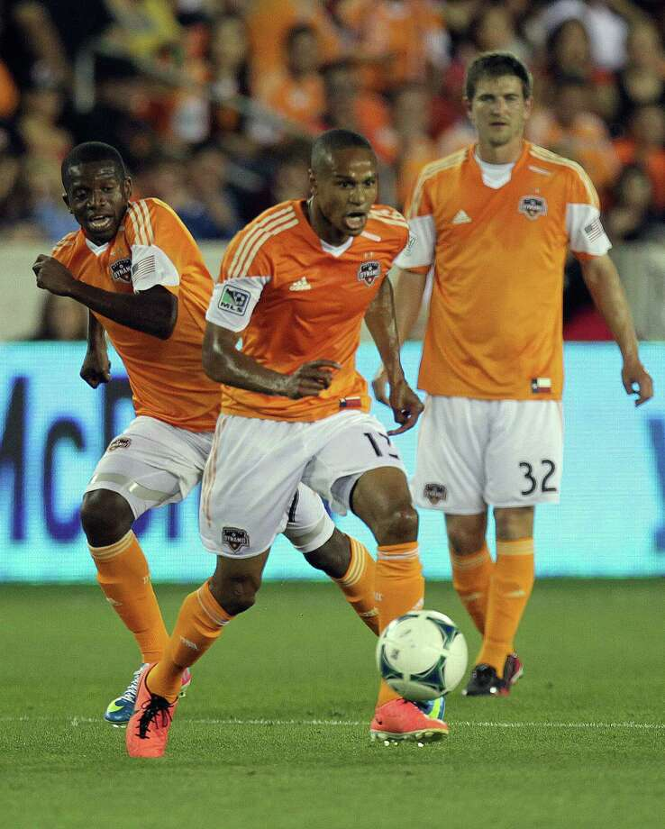 The  Houston Dynamo midfielder Ricardo Clark center, moves the ball against the San Jose Earthquakes as his teammates Boniek Garcia left, and Bobby Boswell right, look on during the first half of MLS soccer game action against the San Jose Earthquakes at BBVA Compass Stadium Saturday, March 30, 2013, in Houston . Photo: James Nielsen, Houston Chronicle / © 2013 Houston Chronicle