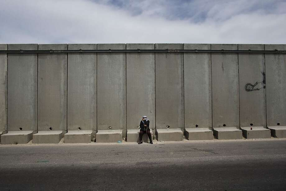 "A Palestinian man pauses near the Qalandia checkpoint between the West Bank city of Ramallah and Jerusalem, Saturday, March 30, 2013. Israeli Arabs and Palestinians in the West Bank and Gaza mark ""Land Day"" Saturday commemorating events in March 1976 when Israel confiscated land from Galilee Arab villages, leading to protests in which six Arabs were killed. The ""Land Day"" rallies are an annual event attended by those who protest what they say are discriminatory Israeli land policies. (AP Photo/Bernat Armangue) Photo: Bernat Armangue, Associated Press"