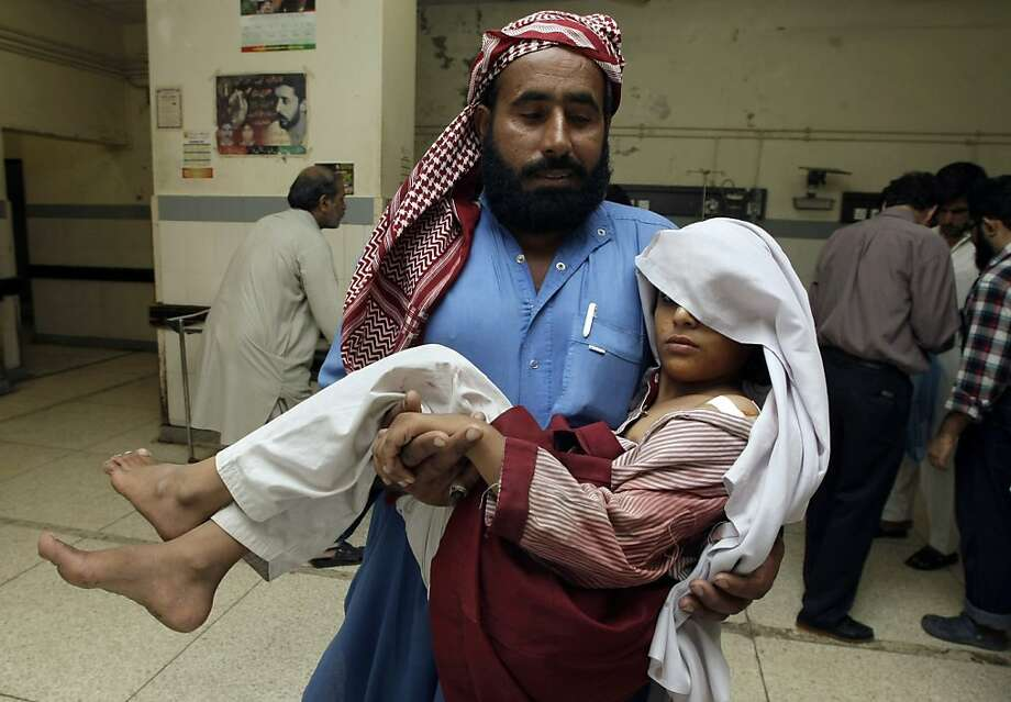 A Pakistani man carries his child who was injured in a grenade attack, inside a local hospital in Karachi, Pakistan on Saturday, March 30, 2013. A man armed with a gun and grenades attacked a school in southern Pakistan during a prize distribution ceremony on Saturday, killing its principal and wounding several children before fleeing. (AP Photo/Fareed Khan) Photo: Fareed Khan, Associated Press