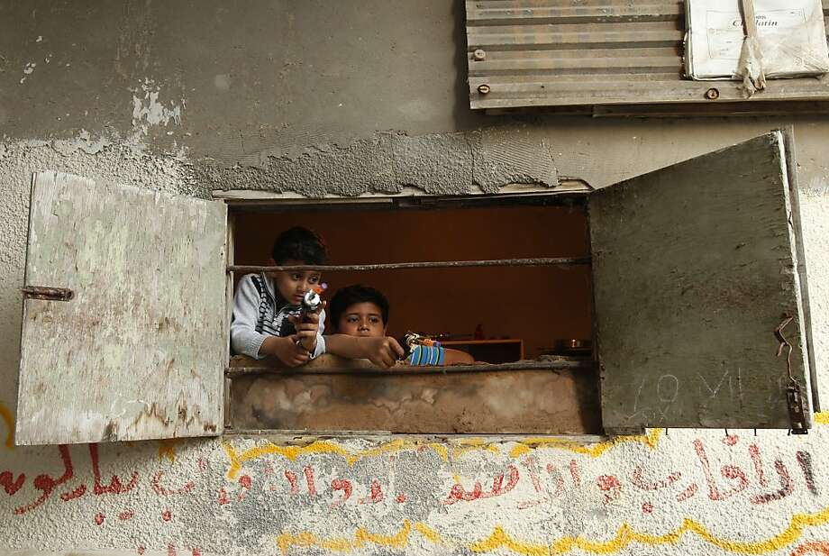 TOPSHOTS Palestinian boys play with toy guns by the window of a house in the Shati refugee camp in Gaza City on March 29, 2013. Palestinians mark Land Day on March 30 to commemorate the death of six Arab Israeli protesters at the hands of Israeli troops during mass protests in 1976 against plans to confiscate land in Galilee. AFP PHOTO/MOHAMMED ABEDMOHAMMED ABED/AFP/Getty Images Photo: Mohammed Abed, AFP/Getty Images