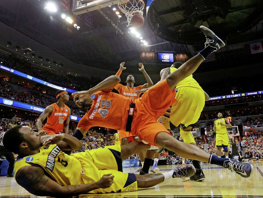 Syracuse forward James Southerland (43) lands on Marquette guard Junior Cadougan (5) as Syracuse center Baye Keita (12) looks for the rebound during the second half of the East Regional final in the NCAA men's college basketball tournament, Saturday, March 30, 2013, in Washington. (AP Photo/Pablo Martinez Monsivais) Photo: Pablo Martinez Monsivais
