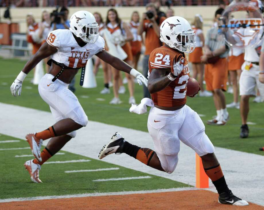 Texas' Joe Bergeron (24) scores a touchdown as Peter Jenkins (19) defends during the NCAA college football team's spring game, Saturday, March 30, 2013, in Austin, Texas. (AP Photo/Eric Gay) Photo: Eric Gay, Associated Press / AP