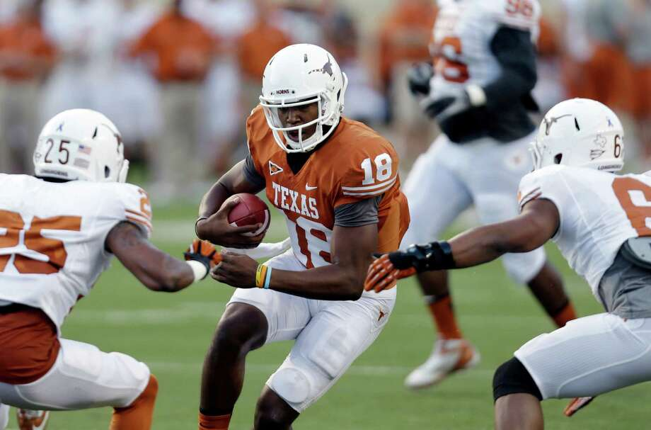 Texas quarterback Tyrone Swoops (18) rushes against Josh Turner (25) and Quandre Diggs (6) during the team's intersquad spring football game, Saturday, March 30, 2013, in Austin, Texas. (AP Photo/Eric Gay) Photo: Eric Gay, Associated Press / AP