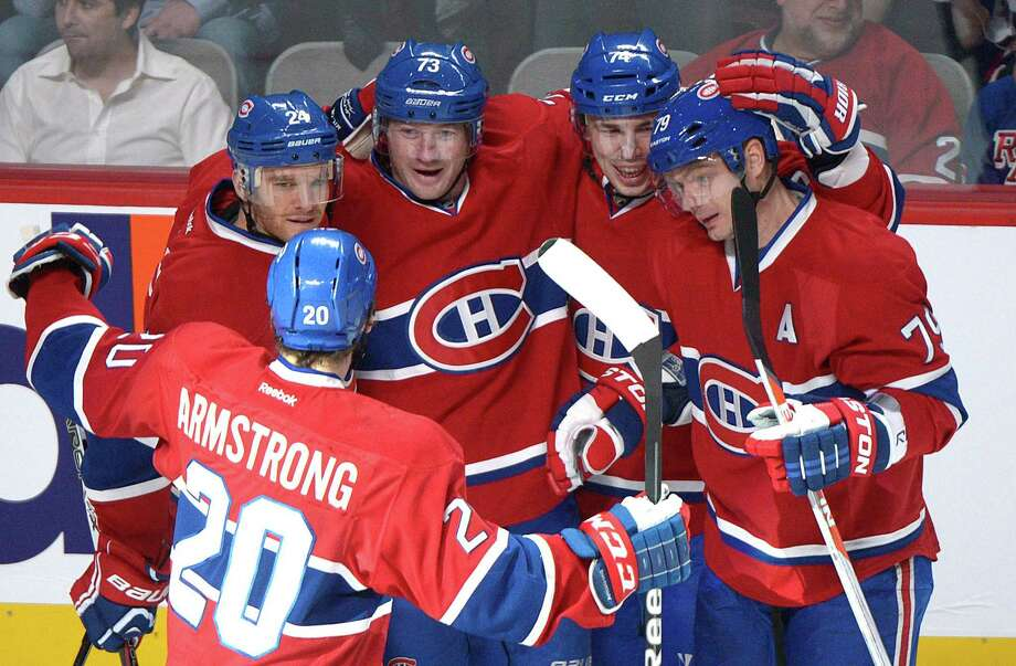 Montreal Canadiens' Michael Ryder (73) celebrates with teammates Jeff Halpern (24), Colby Armstrong (20), Alexei Emelin (74) and Andrei Markov (79) after scoring against the New York Rangers during first-period NHL hockey game action in Montreal, Saturday, March 30, 2013. (AP Photo/The Canadian Press, Graham Hughes) Photo: Graham Hughes