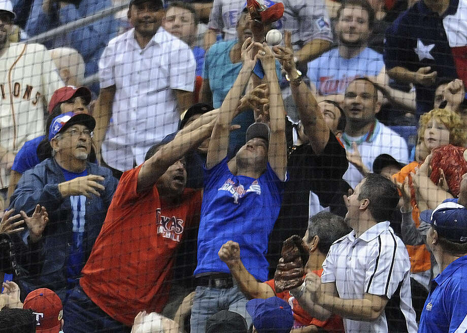 Some of the 40,569 fans battle for a souvenir tossed into the stands during Saturday's preseason game at the Alamodome. Photo: Billy Calzada / San Antonio Express-News