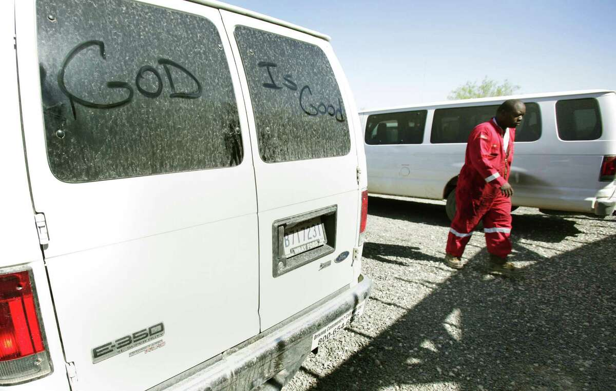 A Halliburton worker passes a company van that someone left a message on while walking toward the dining hall at the Wotel One lodge for oil field workers in Carrizo Springs.
