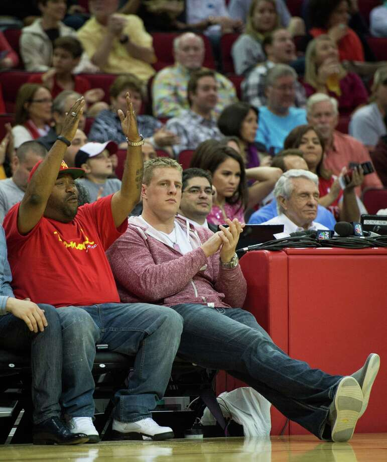 Texans defensive end J.J. Watt, right, and Houston rapper Bun B applaud a defensive play as they sit courtside. Photo: Smiley N. Pool, Houston Chronicle / © 2013  Houston Chronicle