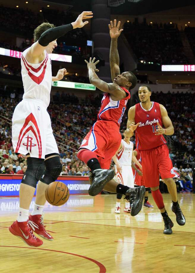 Clippers point guard Eric Bledsoe (12) has the ball knocked away by Rockets center Omer Asik during the second half. Photo: Smiley N. Pool, Houston Chronicle / © 2013  Houston Chronicle