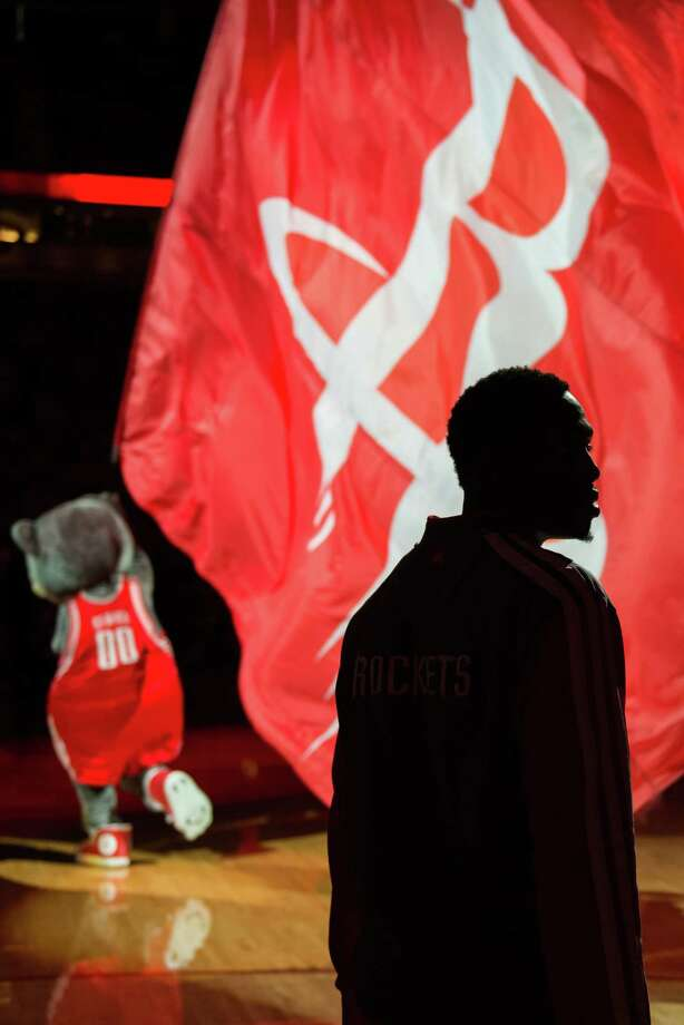 Point guard Patrick Beverley is silhouetted as the Rockets mascot Clutch runs onto the court before the game. Photo: Smiley N. Pool, Houston Chronicle / © 2013  Houston Chronicle