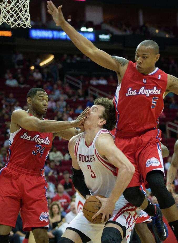 Rockets center Omer Asik is hit in the face by Clippers guard Willie Green as forward Caron Butler comes down on him during the first half. Photo: Smiley N. Pool, Houston Chronicle / © 2013  Houston Chronicle