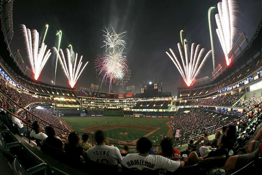Baseball fans look on at a fire works show following a baseball game between the San Diego Padres and Texas Rangers at the Texas Rangers Ballpark in Arlington in Arlington, Texas, Friday, June 26, 2009. The Rangers won 12-2.(AP Photo/Tony Gutierrez) Photo: Tony Gutierrez, Associated Press