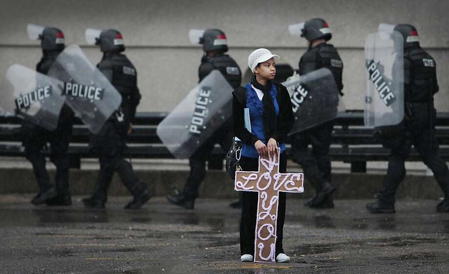 As Memphis Police in riot gear lineup Alvianca McLemore holds a sign of love in a holding area on Adams while waiting for a KKK rally in Memphis, Tenn. Saturday, March 30, 2013. The Ku Klux Klan announced plans to protest in Memphis after the Memphis City Council renamed three Confederate-themed city parks in February. (AP Photo/The Commercial Appeal, Mark Weber) Photo: Mark Weber, Associated Press