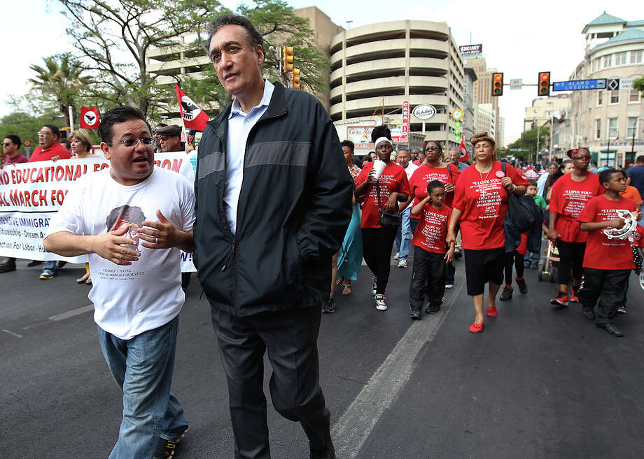 Former HUD Secretary and former city mayor Henry Cisneros talks with Ernest Martinez, chairman of the Chavez Legacy and Educational Fund while marching in the 17th annual Cesar Chavez March for Justice through downtown Saturday, Mar. 30, 2013. Hundreds of people along with and several organizations participated in remembrance of the activist who fought for migrant workers rights. Photo: Kin Man Hui, San Antonio Express-News / © 2012 San Antonio Express-News